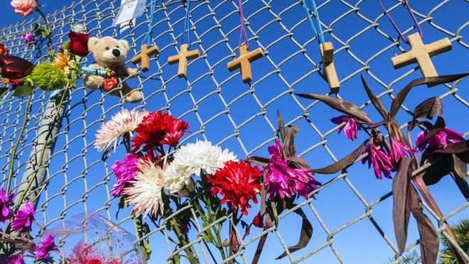 PARKLAND -- Crosses and flowers hang on a fence outside Marjory Stoneman Douglas High School in February 2018, in memory of the 17 people killed in the worst school mass shooting in U.s. history.