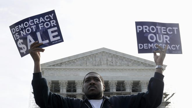 This Oct. 8, 2013, file photo shows Cornell Woolridge of Windsor Mill, Md., as he demonstration outside the Supreme Court in Washington,  as the court heard arguments on campaign finance.