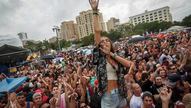 Jessica Hebler, Jupiter, dances in the rain with the crowd at the Dirty Heads performance on the Ford stage at SunFest 2014 in downtown West Palm Beach on Saturday, May 3, 2014.