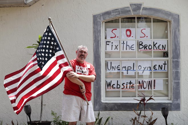 Hew Kowalewski, a furloughed employee of Disney World stands next to a window of his home Monday in Kissimmee. Many of Florida's jobless have reported problems filing applications for unemployment benefits.