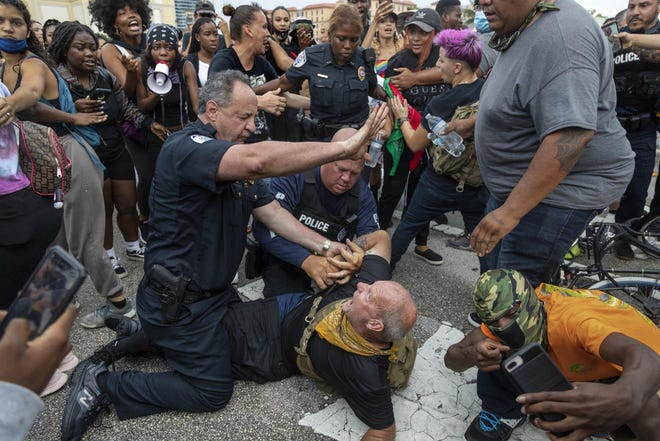 Richard Couse, who was screaming at police officers and peaceful protesters, rode his bicycle through the crowd ignoring several warnings by city police Deputy Chief Rick Morris, left, to leave the area was arrested on June 2, 2020 in West Palm Beach, Florida. Assistant Chief Tameca West back holds the crowd back while officer Mike LeMoine, center, helps restrain the man. The marchers were protesting the death of George Floyd.
