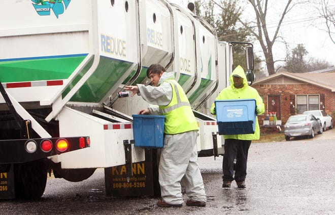 Schuyler Smith, left, and Josh Trammell,with the City of Tuscaloosa Environmental Services Department Curbside Recycling, pick up recyclables in the rain on in the Lincoln Park neighborhood Monday, Dec. 10, 2012.