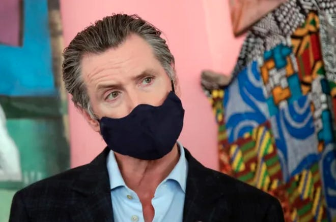 In this June 9, 2020, file photo, California Gov. Gavin Newsom wears a protective mask on his face while speaking to reporters at Miss Ollie's restaurant during the coronavirus outbreak in Oakland, Calif.