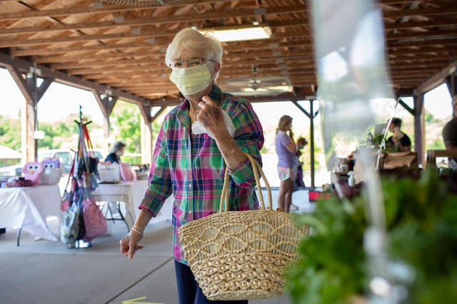 Jane Speakman shops on the opening day of the Columbia Farmers' Fresh Market at Riverwalk Park on Saturday.