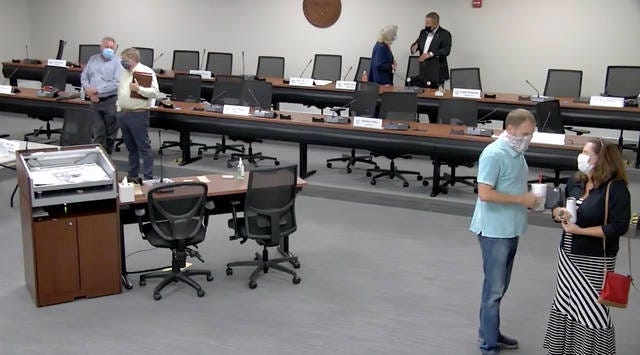 Maury County commissioners Scott Sumners and Michelle Haney speak while wearing masks inside the Tom Primm Commission Meeting Room after approving the county budget on June 30, 2020.