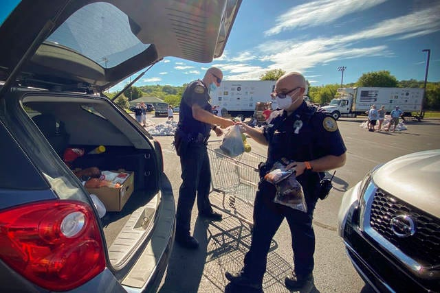 Columbia Police Department officers Ryan Langhi and Matthew Burns volunteer at the One Gen Away food giveaway at Columbia State Community College on Saturday.