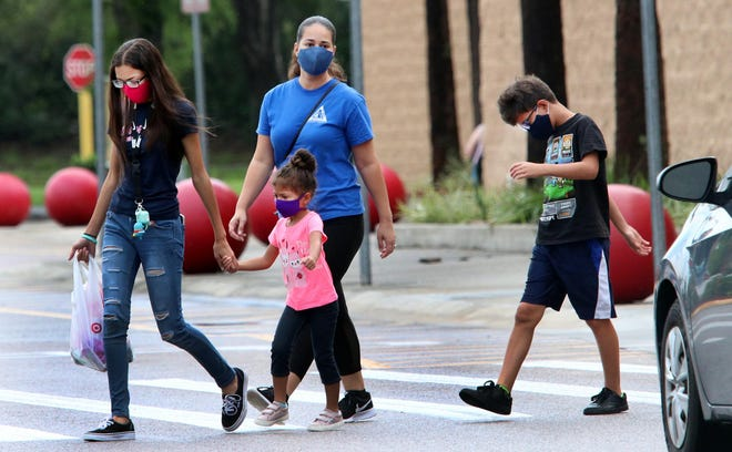 Shoppers wearing face masks exit the Target store in Orange City on Wednesday, July 8, 2020. The City Council on July 6 voted to approve an ordinance mandating the wearing of face coverings amid the coronavirus pandemic.