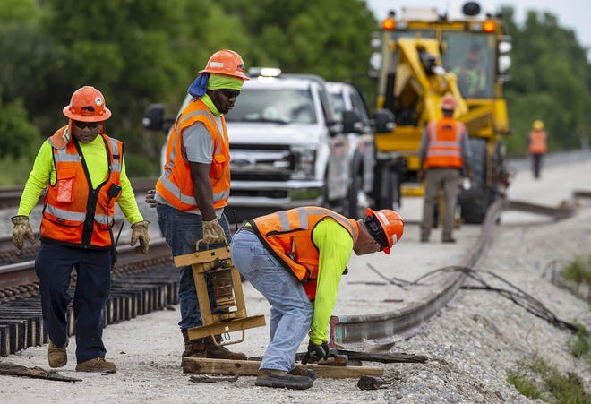 Brightline construction crews position a rail north of Hood Road on Aug. 7 in Palm Beach Gardens. Brightline is adding a second set of tracks for its planned expansion to Orlando.
