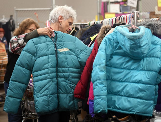Cuyahoga Falls Good Neighbors volunteer Lisa Goldstein adds a winter coat on the rack. Good Neighbors has announced they will be open on Wednesday evenings in addition to their daytime hours on Tuesday and Thursday.