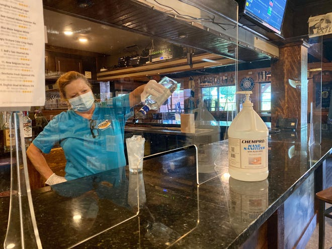 An employee at Jubilee Restaurant in Pocono Pines makes a drink behind a partition installed along the bar in August, 2020. The Wolf administration recently announced millions of dollars in recovery grants for businesses impacted by the coronavirus pandemic, made possible by the COVID-19 Hospitality Recovery Program.
