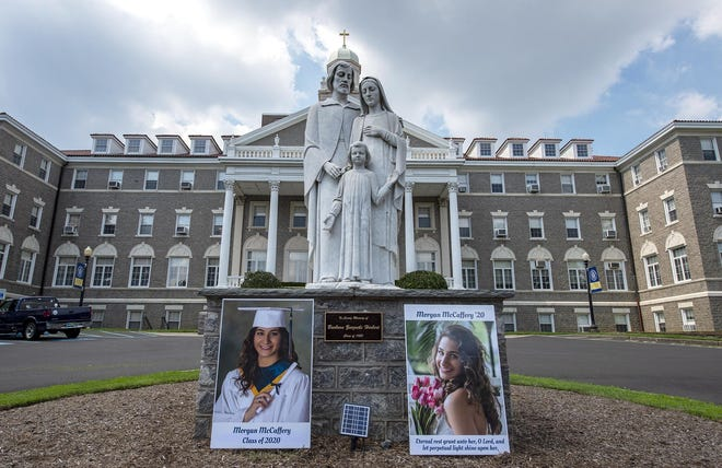 Photos of dating violence victim Morgan McCaffery, a 2020 graduate of Nazareth Academy in Philadelphia, rest next to the Holy Family statue in front of the high school.