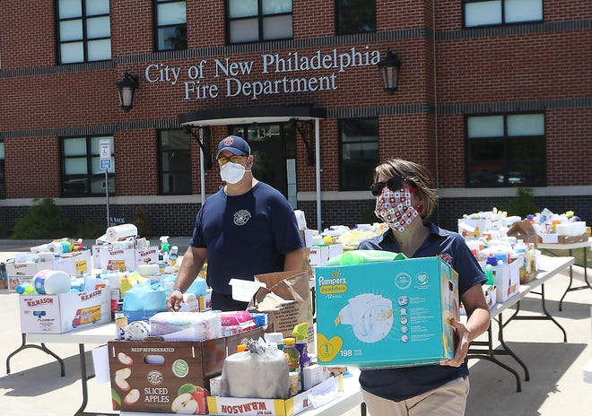 New Philadelphia firefighter Nick McCoy and administrative staff member Denise Phillips work at distributing household items in front of the station for the fire department's Compassion Station project in July.