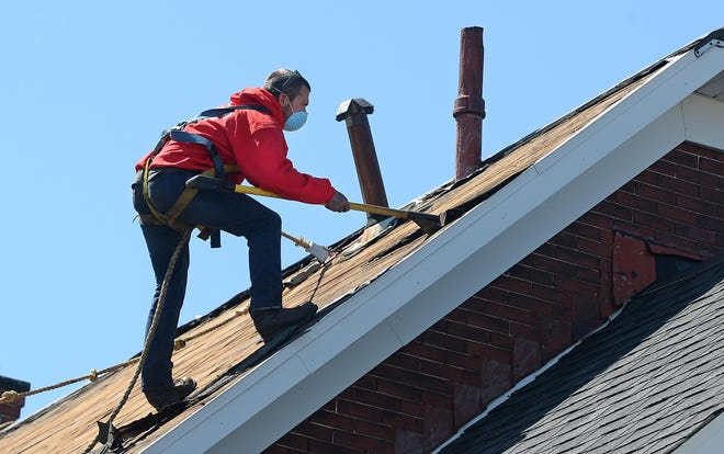 Cody Haines, a roofer with Angelo's Roofing and Construction Inc., tears a roof off a home at 138 W. 25th St. on May 13. The company had to reduce its workforce during the COVID-19 shutdown, but is back to a full crew of 25.