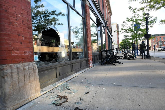 Broken glass windows are shown in the Ember + Forge coffee shop in the 400 block of State Street on Sunday. The damage occurred late Saturday following a peaceful protest in response to the killing of George Floyd, a black man who died at the hands of Minneapolis police on May 25.