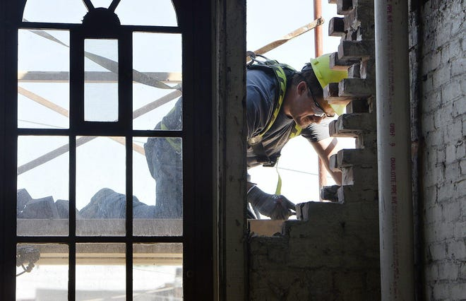 Derrick Parsons chips old mortar this summer to loosen bricks while helping renovate property owned by the Erie Downtown Development Corp. Sen. Tim Scott, of South Carolina, will pay a virtual visit to Erie Wednesday to highlight the EDDC's work on Opportunity Zones.