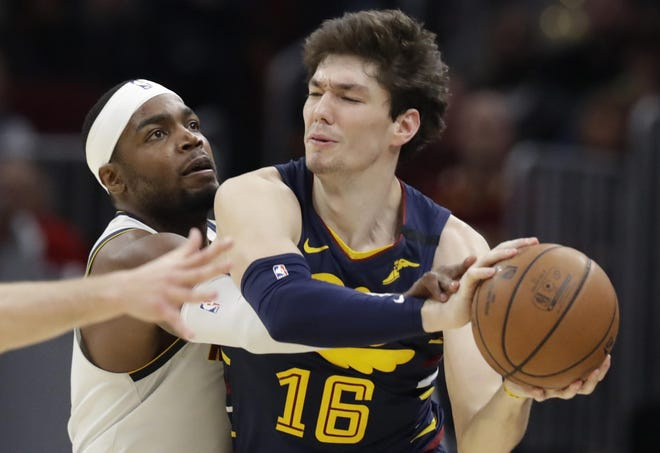 The Denver Nuggets' Paul Millsap, left, tries to knock the ball loose from the Cavaliers' Cedi Osman in the second half of a game in March. [Tony Dejak/Associated Press file]