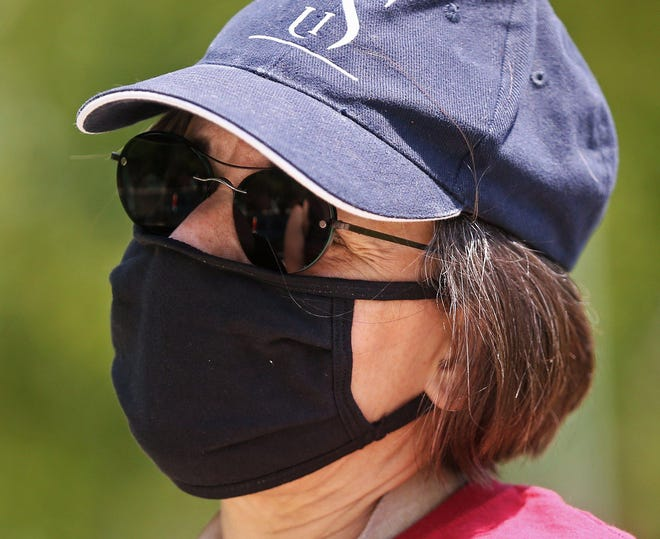 A member of the faculty union at the University of Akron wears a mask in 2020 during a protest against planned cuts. On Tuesday, regional hospitals joined the Summit County Public Health Department in advising that everyone should wear a mask indoors, including schools, regardless of vaccine status, with the rise in the delta variant.