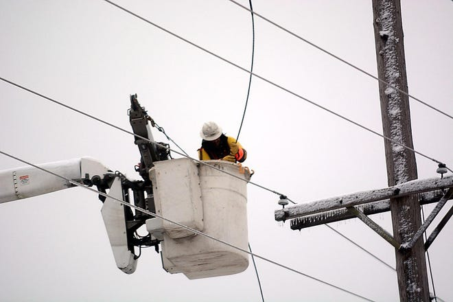Inside a bucket above the the street, a lineman for Ohio Edison gets ready to reconnect a wire that came down in 2018 in front of Hoover Price Campus Center at Mount Union in Alliance.