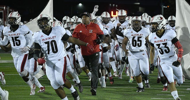 McKinley head coach Marcus Wattley runs onto the field with his team prior to the Bulldogs' 2019 Week 9 win at Perry.