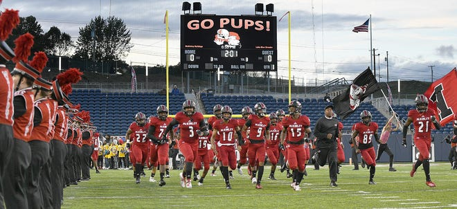 The McKinley High School football team takes the field. The Canton City school board is considering whether to lower the minimum grade point average for student athletes from 2.0 to 1.5.