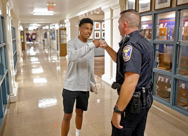 Worthington Division of Police officer Sean Ord greets Thomas Worthington High School 2018-19 senior Noah Tennant on Aug. 16, 2018. The Worthington school board on July 27 voted 3-2 for a motion to keep the district's two full-time SROs from returning to the halls of Thomas Worthington and Worthington Kilbourne high schools, leading to a request to open dialogue regarding their future, according to Assistant Superintendent Randy Banks.