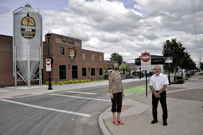 Libby Gierach (left), president and CEO of the Hilliard Area Chamber of Commerce, and Tim Kauffman, executive director of Destination Hilliard, stand at Hilliard's Station Park along Center Street in Old Hilliard in June 2020. Kauffman died May 30 at his home. He was 64.