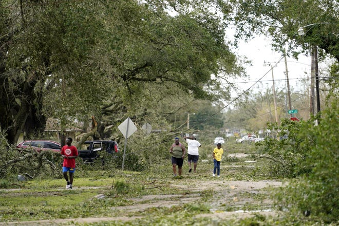People survey the damage to their neighborhood on Thursday, Aug. 27, 2020, in Lake Charles, La., in the aftermath of Hurricane Laura.