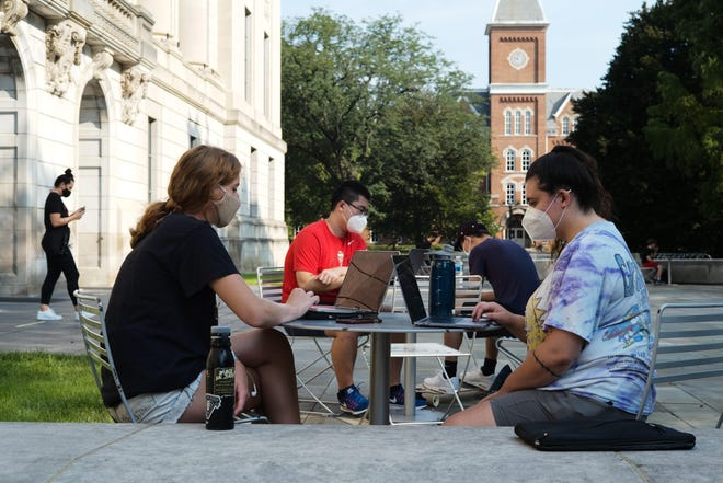 Students stay busy during the first day of fall classes on Tuesday at Ohio State University. The school is using a mix of virtual and in-person learning because of the ongoing COVID-19 pandemic.