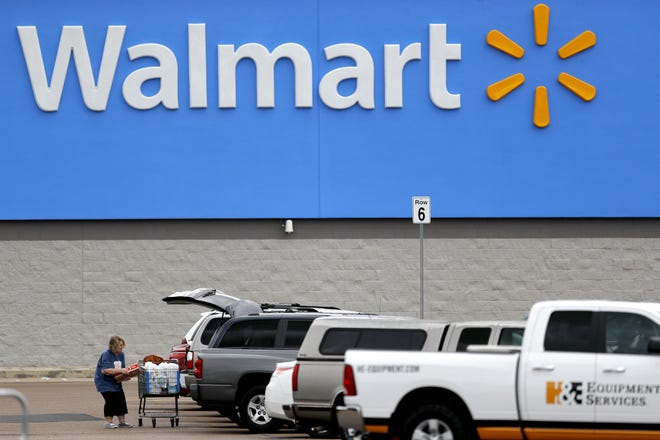 In this March 31, 2020 file photo, a woman pulls groceries from a cart to her vehicle outside of a Walmart store in Pearl, Mississippi.Walmart is launching a new membership service that it hopes can compete with Amazon Prime.