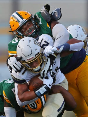 Hoban running back Victor Dawson, center, carries St. Ed defensive lineman Thomas Aden on his back as he rushes for a first down during the first quarter of a football game at First Federal Lakewood Stadium, Saturday, Sept. 5, 2020, in Lakewood, Ohio.