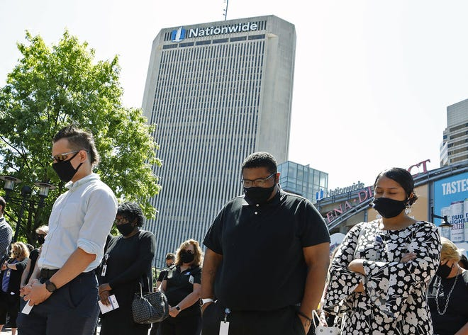 "Nationwide employees Michael Kubica, Devonne Sheppard and Shanice Mock, from left, observe a moment of silence for George Floyd at the Nationwide ""Standing in Unity, Moving Forward Together'' rally on June 12."