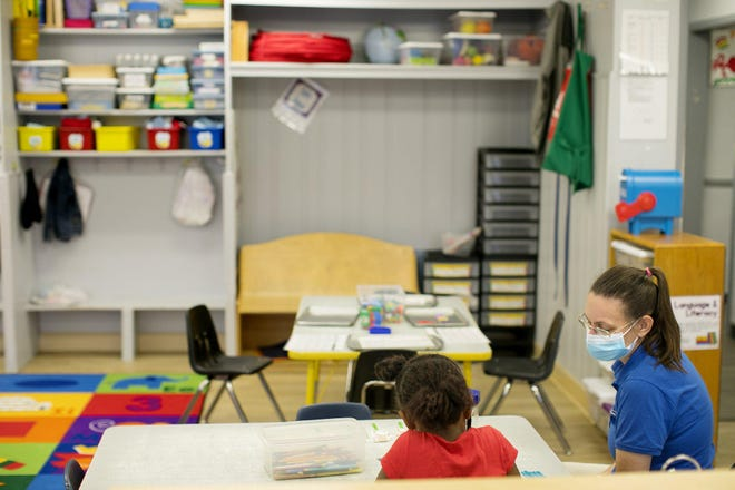 Cathy Martz works with a child in the preschool room at Creative Child Care's center on Shanley Drive off Karl Road on Thursday. The center is running at about 40% capacity, and day care providers can receive a yet-to-be determined subsidy if they choose not to run at full capacity.