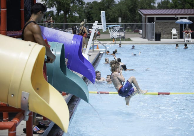 Eric Drummond holds his nose as he flies out of a tube into the City Park swimming pool in 2019.