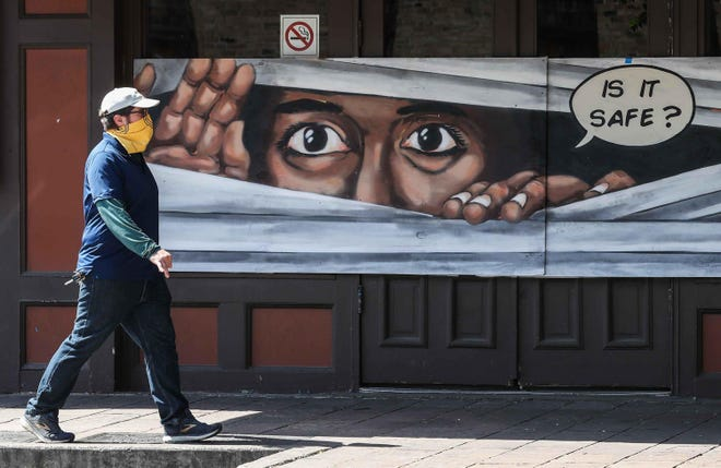 A man walks in front of a mural on Sixth Street wearing a mask amid the coronavirus pandemic. New figures from the Federal Reserve Bank of Dallas indicate the Austin-area economy contracted at a record pace in April, the first full month of the pandemic's impact on the economy.
