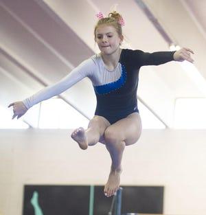 Pueblo Central co-op gymnastics team member Hailey Garner lands a jump during her balance beam routine at a meet at Nogare's Gym.