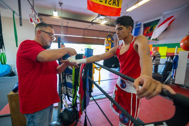 Gil Trujillo wraps the hands on Anthony Soto before a July 2020 training session in Pueblo.
