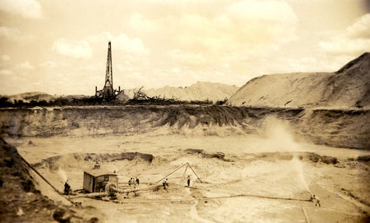 Swift & Co. miners creating slurry with pressurized water at a phosphate rock mine, photo dated 1941