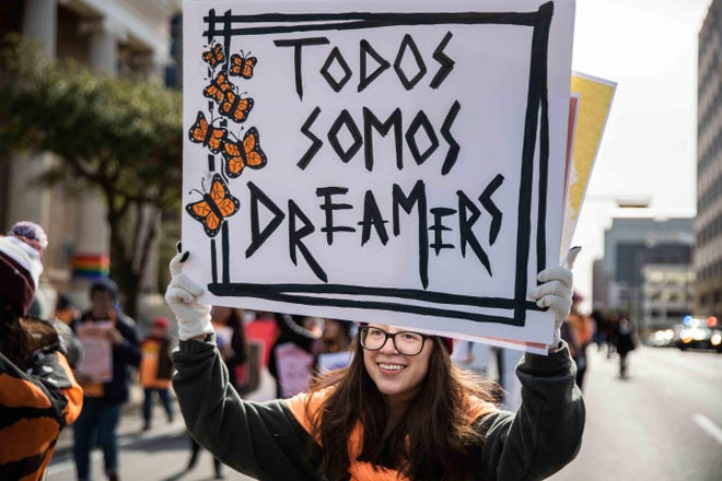 """Brenda Godoy holds a banner that says, """"Todos Somos Dreamers"""" (""""We all are Dreamers""""), during an Austin rally in 2019."""