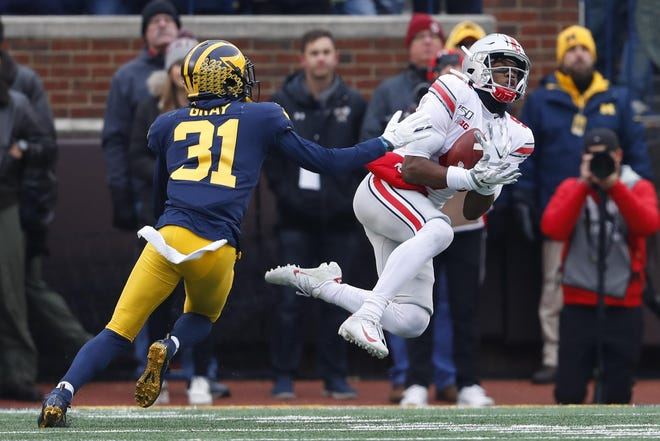 Ohio State wide receiver Garrett Wilson catches a pass as Michigan defensive back Vincent Gray defends during their teams' matchup in 2019. The Big Ten conference announced Thursday that its schools will not play nonconference games in 2020.