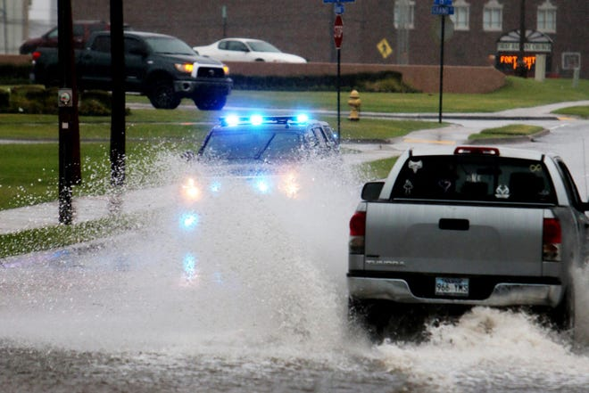A truck passes through the flooded intersection at Grand Avenue and N. 16th St., Thursday, July 9, 2020, during a morning thunder storm in Fort Smith. Friday's forecast calls for partly cloudy skies with a 20 percent chance of rain and a high of 99 degrees.