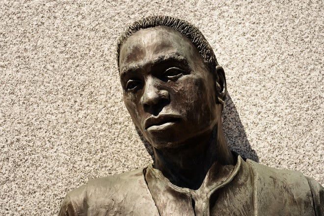 The sculpture at the entrance of the African Burying Ground Memorial Park in Portsmouth was created by sculptor and artist Jerome Meadows and landscape artist Roberta Woodburn.