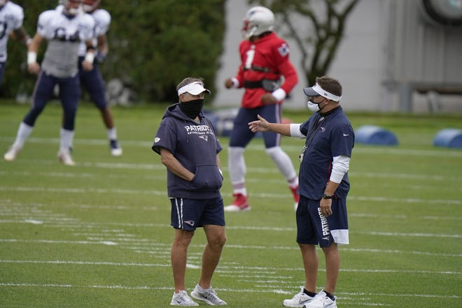 New England Patriots head coach Bill Belichick, left, and New England Patriots offensive coordinator Josh McDaniels, right, confer during an NFL football training camp practice, Monday, Aug. 17, 2020, in Foxborough, Mass.