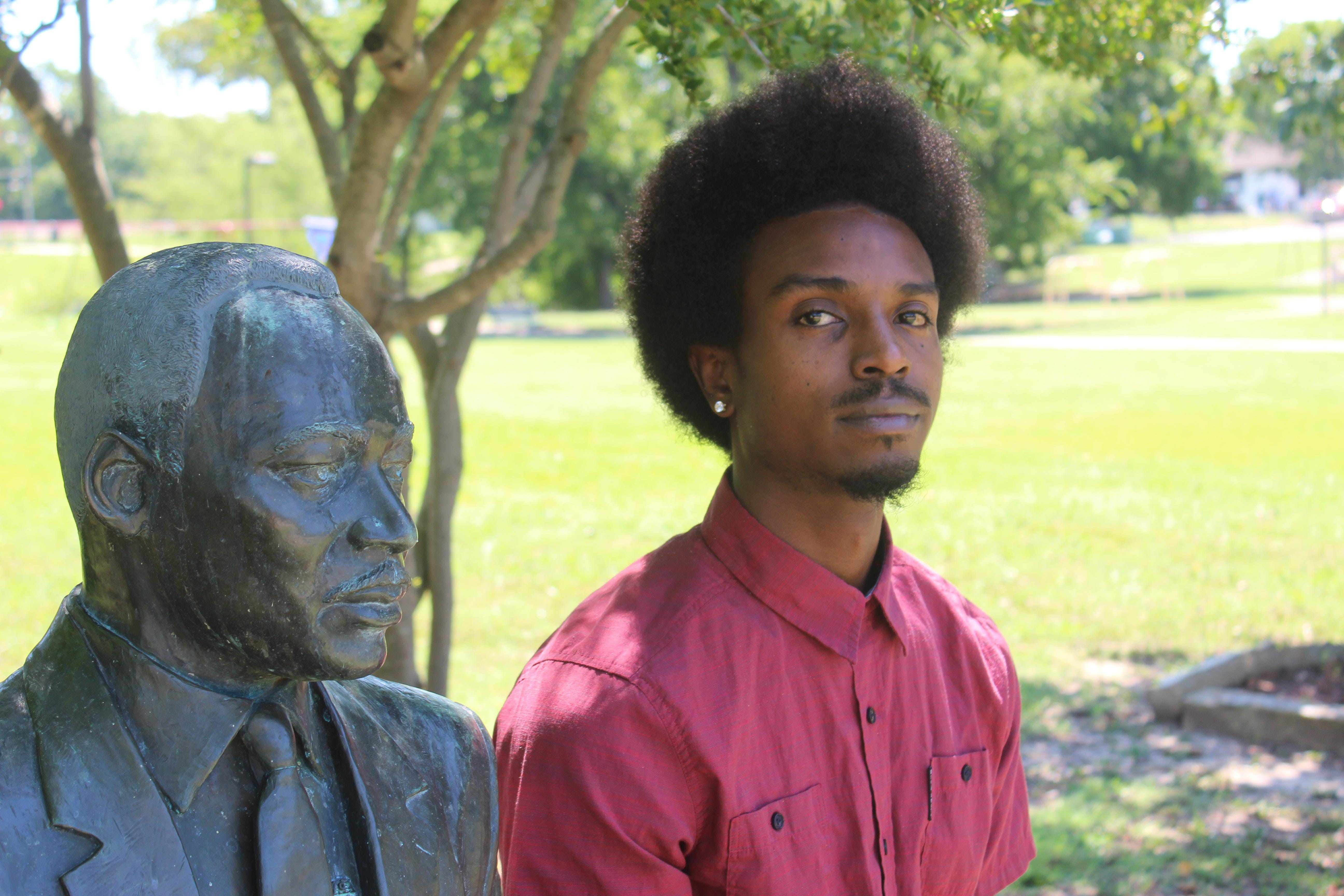 Joshua Shaw sits next to the Martin Luther King Jr. statute at East Street Park in Sherman on Aug. 2.