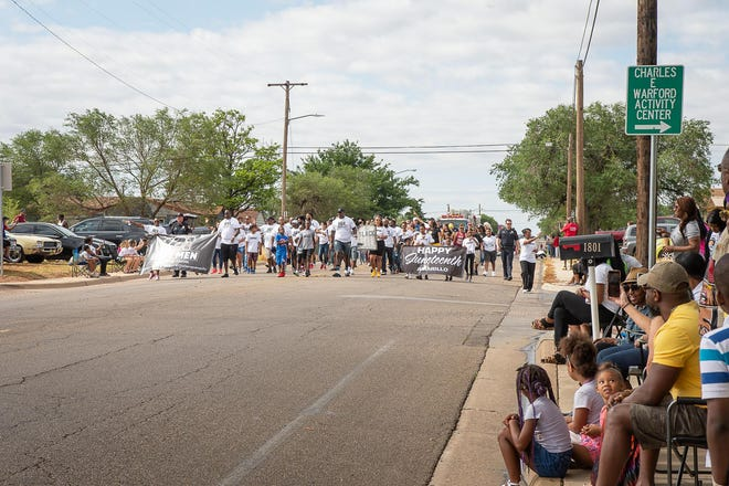 Community members participate in a Juneteenth parade and celebration in the North Heights Neighborhood in the Globe-News file photo.