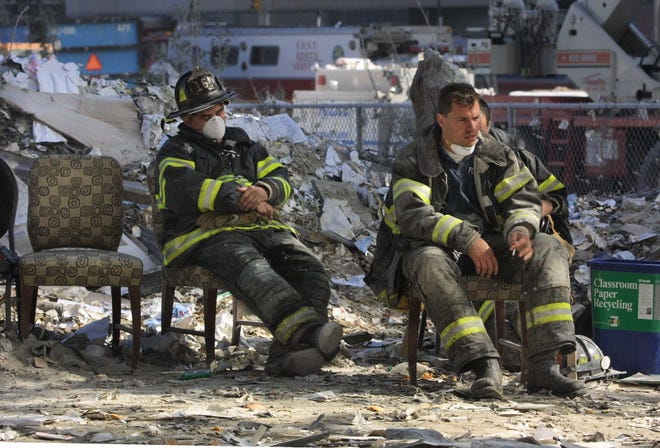 Emergency personnel catch a break during the cleanup operation at the World Trade Center after the towers were demolished by a terrorist attack on September 11, 2001.