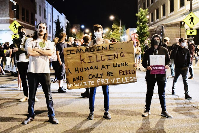 A group of protesters stands in the street during a protest on Monday night in downtown Columbia.