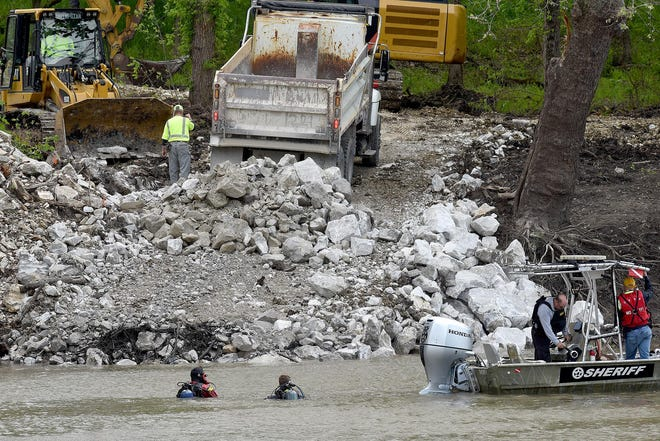 Workers in May dump rock on the bank of the Lamine River in Cooper County to create a temporary levee to allow a more extensive search for Mengqi Ji, who has been missing from her Columbia home since October.