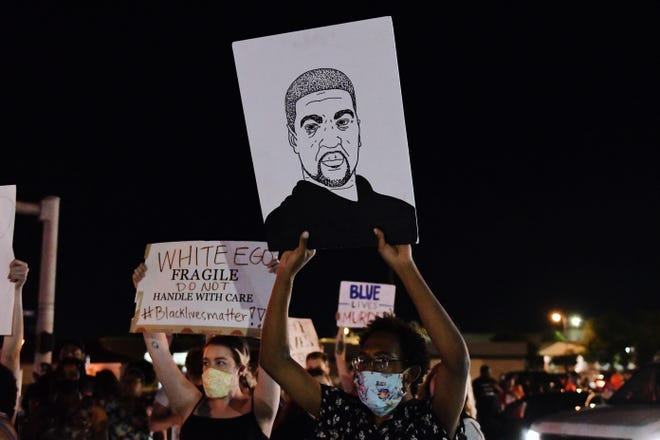 A man holds up a drawing of George Floyd during a protest in Columbia last year against police violence.