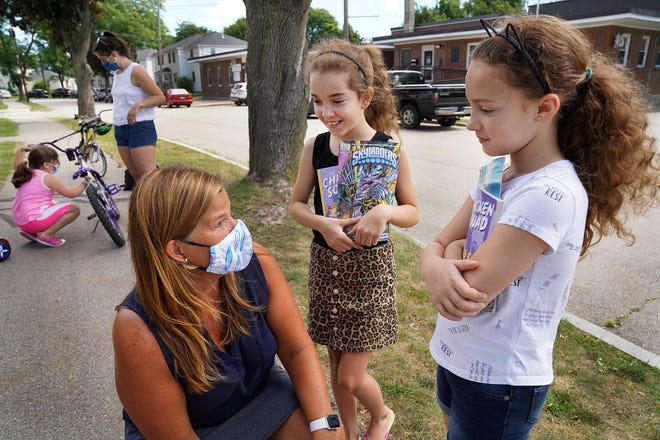 Donna Turco, reading specialist at New Franklin School, visited with Andrea Hatch and her sister Aleeyah Kimber during book deliveries to Portsmouth's Gosling Meadows neighborhood last summer.
