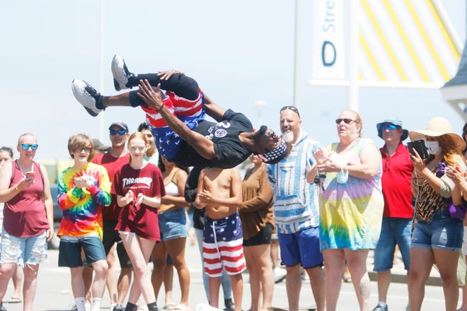 Onlookers applaud as a member of the YAK dancers of Boston performs in front of the Casino Ballroom at Hampton Beach on July 4th, 2020.